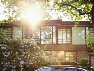 Outside street view of a modern home, back lit but the sun and surrounded by leafy foliage.